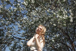 Spring beautiful romantic girl, blonde, standing in a blooming Apple orchard. Sensual girl pleasuring blossoming spring with closed eyes