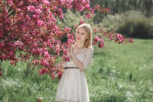 Beautiful young blonde woman enjoying sunny day in park during cherry blossom season on a nice spring day