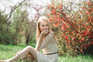 Happy blonde woman in spring sitting in a blooming garden and enjoying nature
