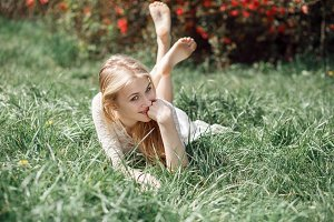 Outdoor portrait of beautiful blonde girl lying on green grass