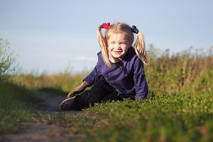 Funny little girl on a country road in the field. The child smiles happily