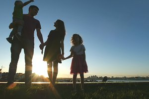 Portrait of happy family at sunset - father, mother, daughter and little son - silhouette