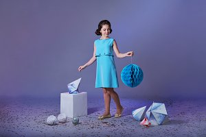 Pretty girl in an elegant blue dress for teenage girls with a make-up. Origami and minimalism. Fashion children.