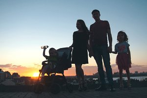 Family at sunset - father, mother, daughter and little son - silhouette