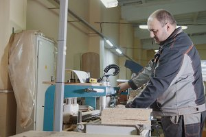 Carpenter cut a wooden workpiece on a furniture factory