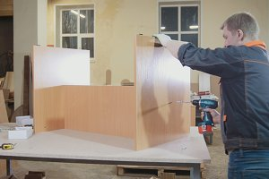 Worker carpenter is screwing chair leg at a furniture factory