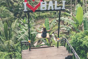 Young woman swinging in the jungle rainforest of Bali island, Indonesia. Swing in the tropics.