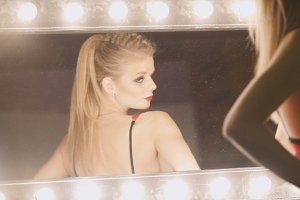 Young blonde woman in red underwear looking at mirror - posing for photographer