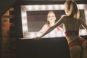Young pretty blonde woman in red underwear looking at mirror - posing for photographer