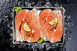 Salmon steaks on ice on black background