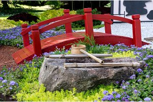 Red wooden bridge and a well. The Japanese village.
