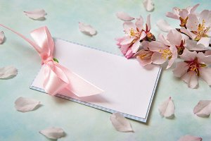 Blank card among almond flowers on l
