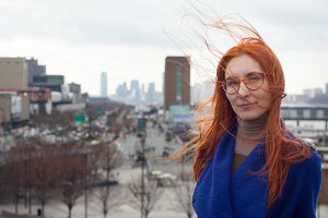 Young cute red-haired woman in a blue coat and glasses standing on the background of the big city, her hair fluttering in the wind