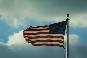 Waving usa flag in front of cloudy sky