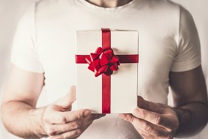 Gift box in hands with red ribbon