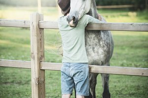 Young guy hugs his friend's horse