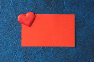 Red blank card on blue with a heart