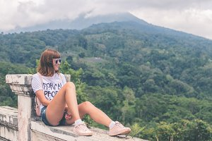 Beautiful young woman in sunglasses and with backpack on tropical jungle background. Bali island, Indonesia. Asia.