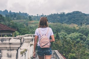 Beautiful young woman with backpack on tropical jungle background. Bali island, Indonesia. Asia.