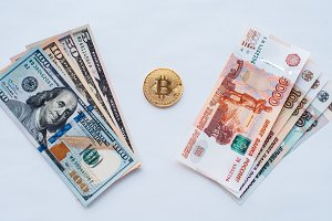 On white background, the exchange of Russian rubles on US dollars on a metal coin bitcoin in paper money from crypto currency.