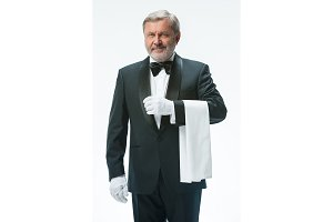 Senior waiter holding white towel