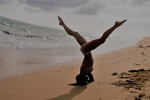 girl stands on her head on the beach