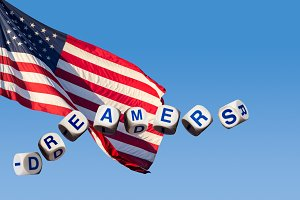 Dreamers concept using spelling letters against blue sky and flag