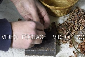 Chipping the hazelnuts with a hammer on the table