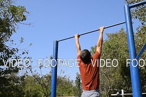 man pulls himself up on the bar. Playing sports in the fresh air. Homemade Horizontal bar in the backyard.
