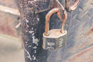 Closeup of a closed rusty padlock on metal door. Balinese temple. Bali island, Indonesia.