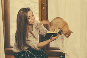 Girl reading book and play with cat