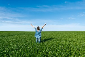 Woman with raised hands in the field