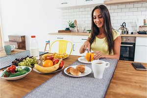 Breakfast with fruits, orange, coffee and croissant. Woman sitting at kitchen table