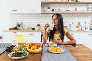 Young woman drinking coffee at home in the morning.