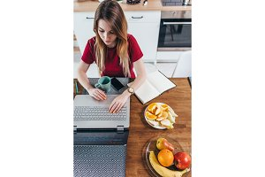 Woman working in kitchen with laptop. Home remote work