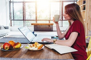 Woman sitting at table in the kitchen and working with laptop