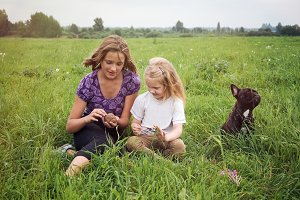 Children and dog sitting in the middle of green fields