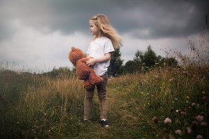 The girl with plush bear. Stormy sky, tall grass fields