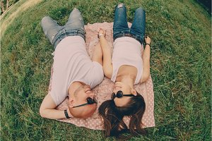 pair of young lovers lie on the grass and smile