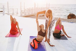 Group women doing yoga at sunrise