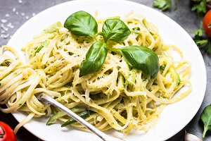 Pasta spaghetti with zucchini basil and cheese.