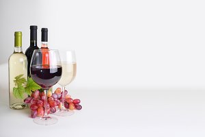 bottles of wine, wineglass and grape