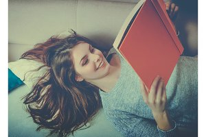 Smiling girl reads a book at sofa