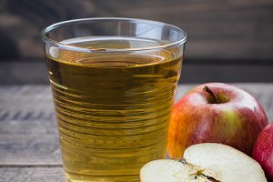 Glass of apple juice with red apples