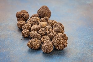 Black truffles on a colored wooden surface