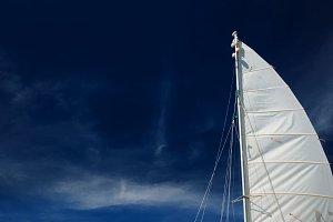 Sail boat, catamaran, on tropical beach with blue water