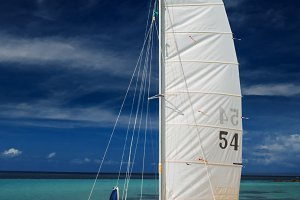 Sail boat, catamaran, on tropical beach with blue water