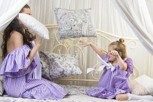 Mother with daughter pillows fight