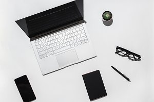 Modern White office desk table with laptop, blank screen smart phone, stylish eyeglasses, black notebook and pen. Top view with copy space.