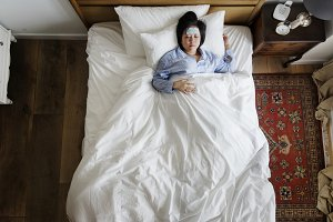 Woman with fever sleeping on bed